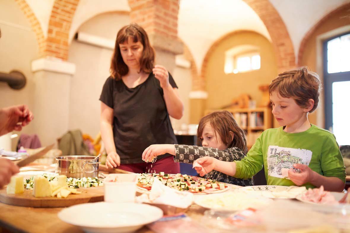 Eine Frau und zwei Kinder bestreuen Pizzateig mit Käse.