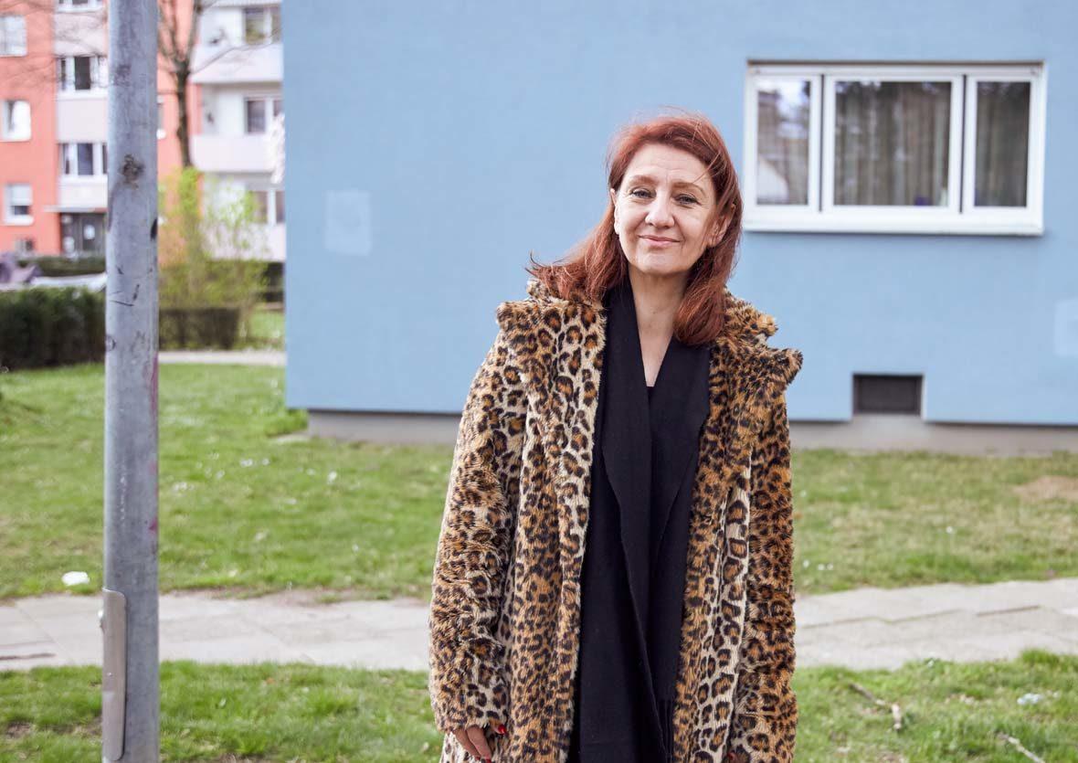 Frau mit Kunstfellmantel steht vor einem Wohnhaus.
