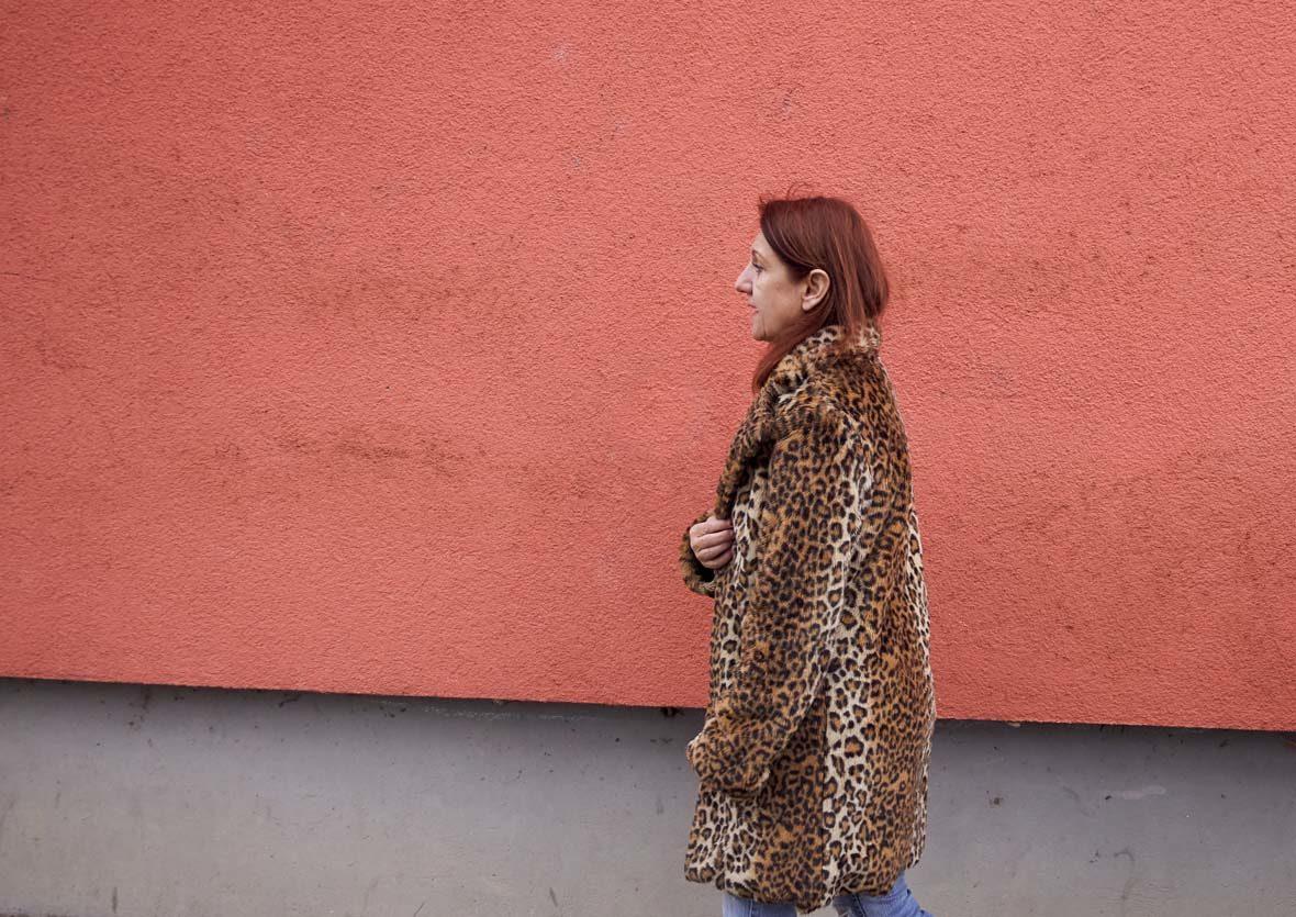 Frau im Kunstfellmantel läuft an Hauswand vorbei.