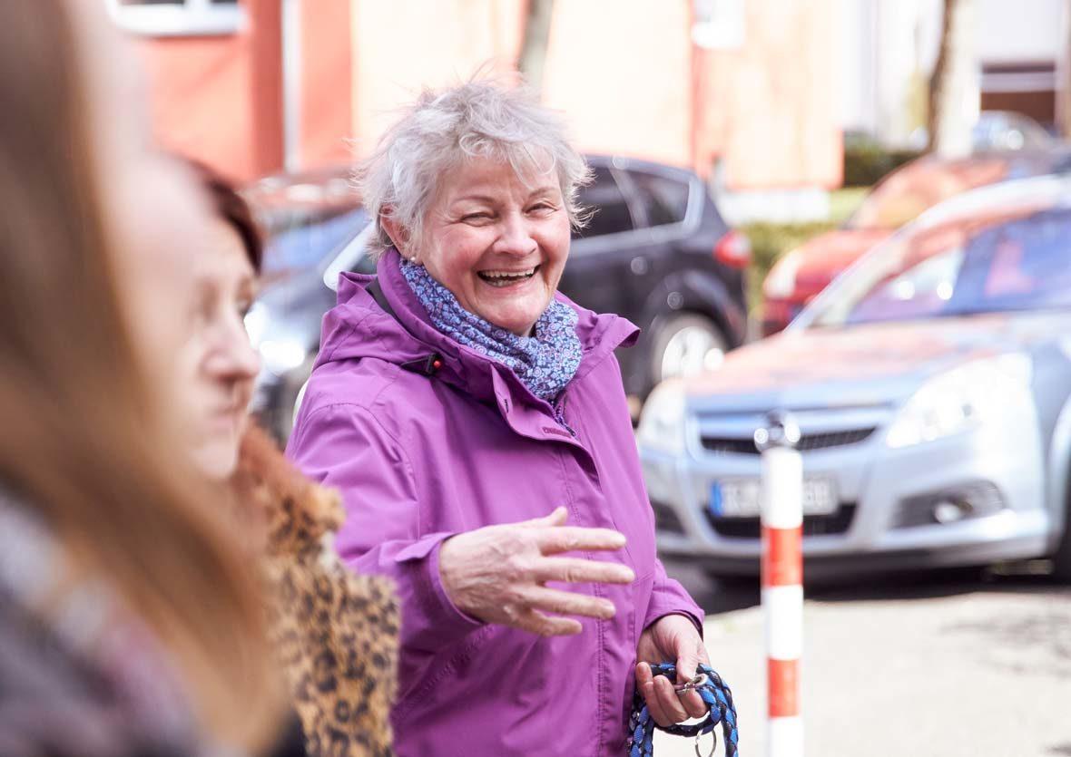 Eine ältere Frau hält eine Hundeleine in der Hand und lacht.