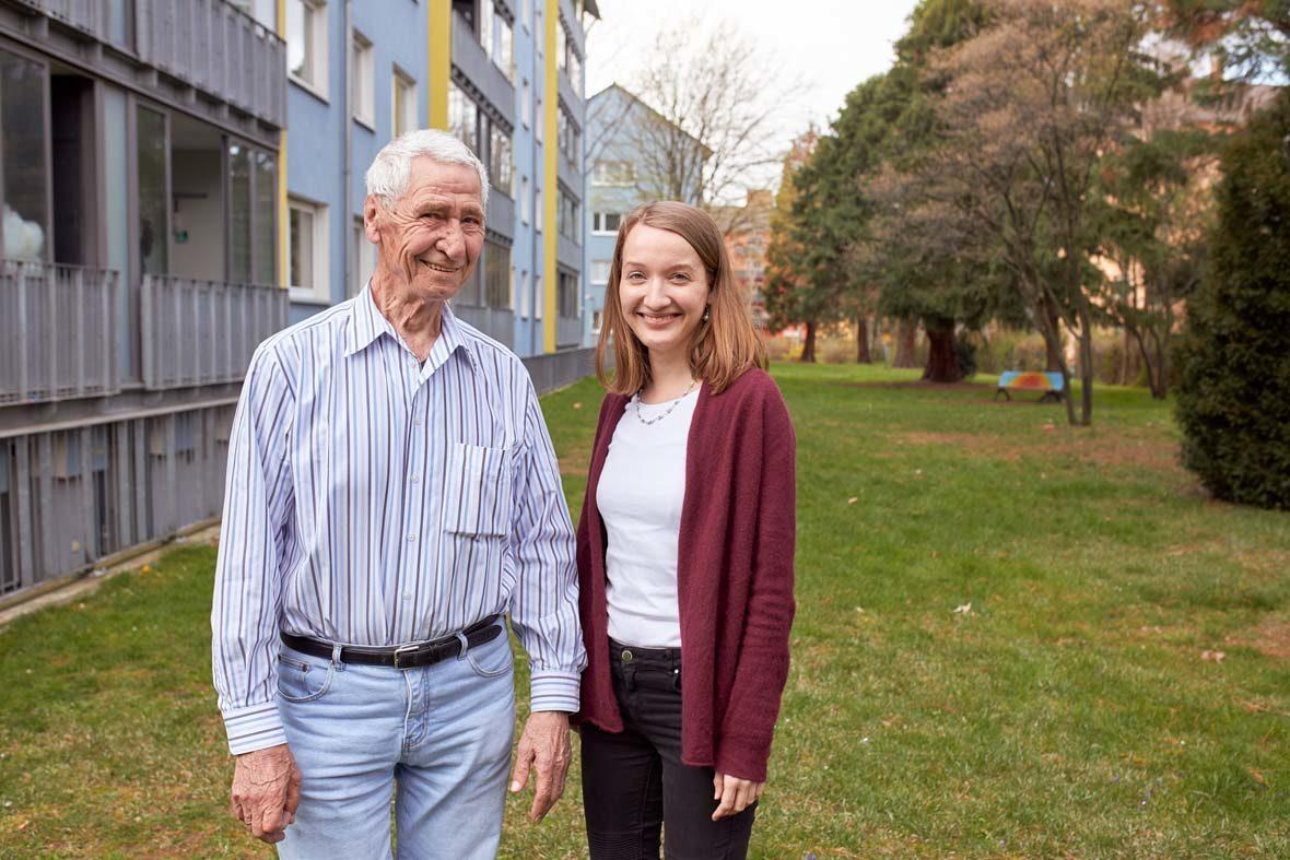 Ein älterer Mann und eine junge Frau stehen auf der Wiese vor einem Wohnhaus.