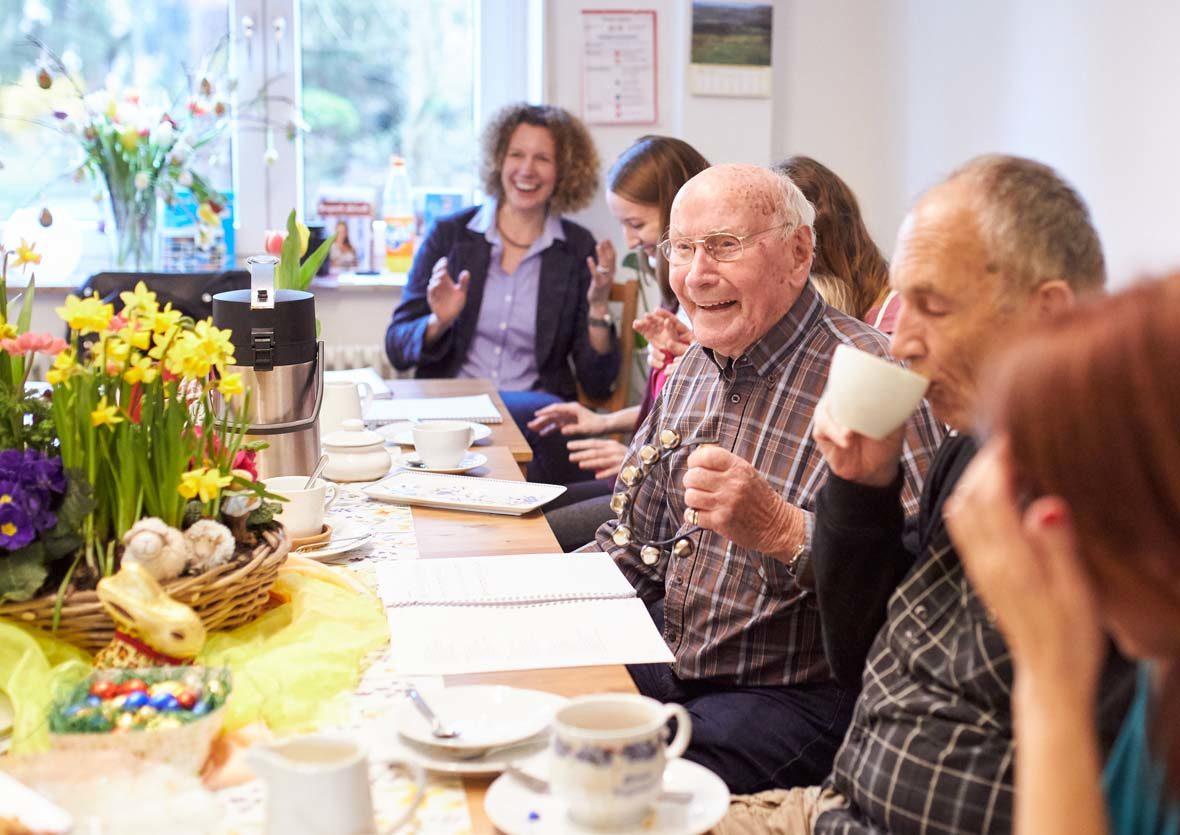 Mehrer Menschen sitzen an einem Tisch, trinken Kaffee und singen.