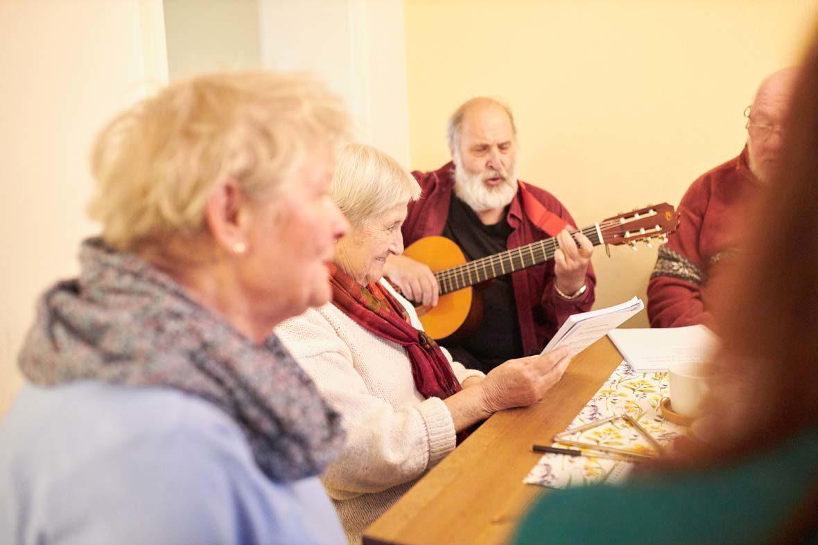Ein älterer Mann sitzt mit mehreren Menschen am Tisch und spielt Gitarre.