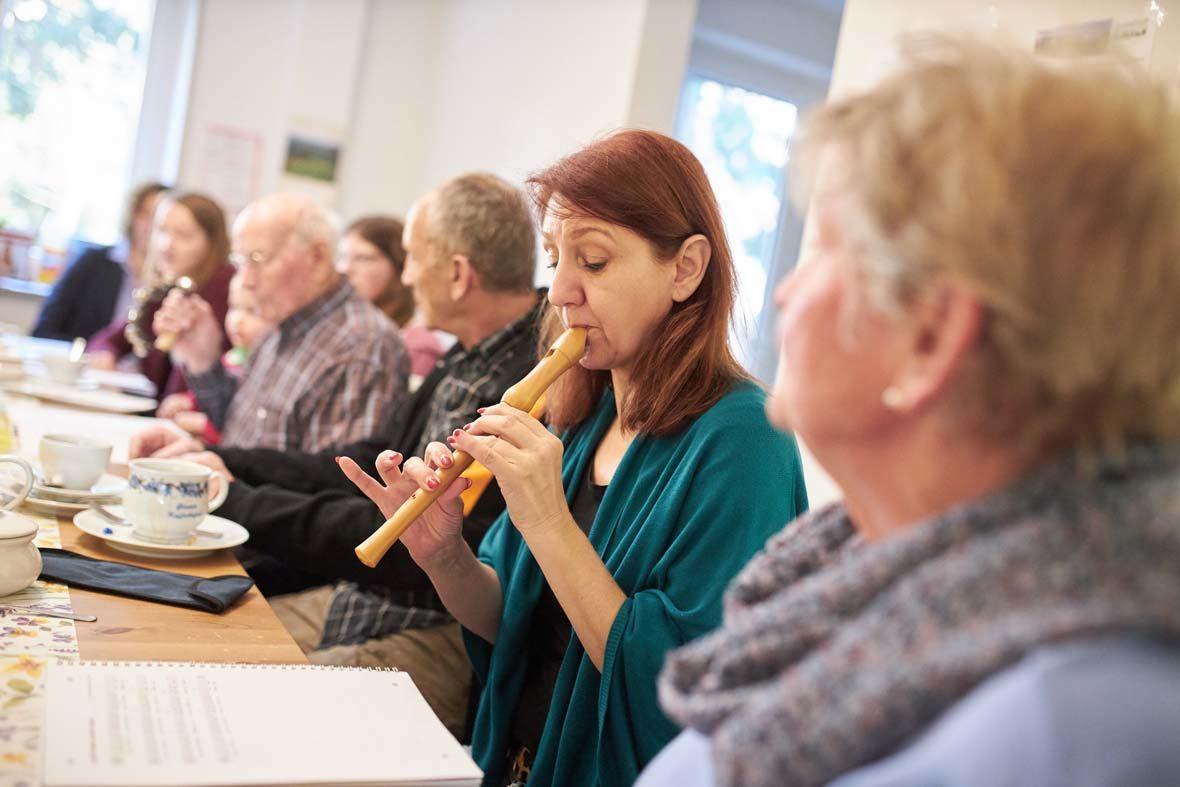 Eine Frau sitzt mit mehreren Menschen am Tisch und spielt Flöte.