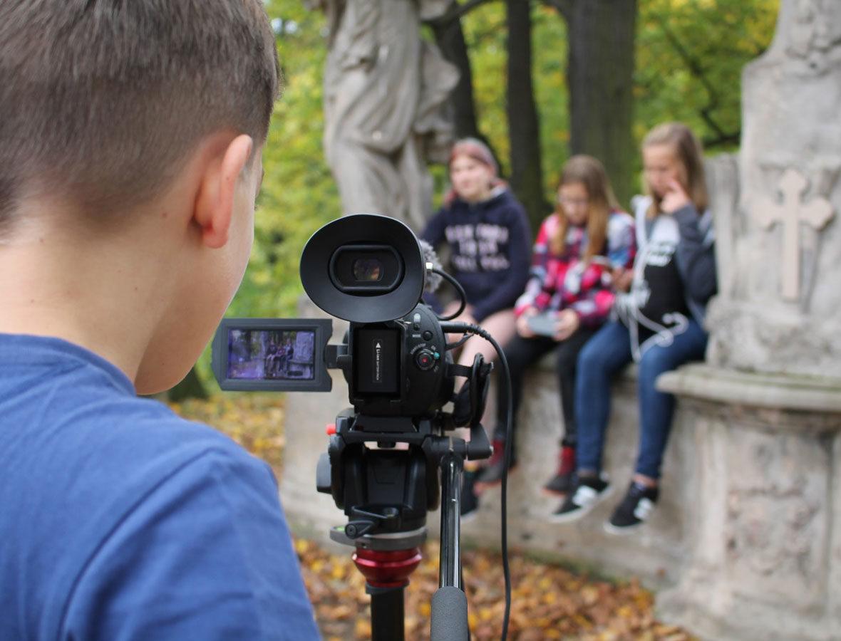 Foto: Junge steht vor Filmkamera, schaut hinein und Filmt drei Mädchen, die auf einer Mauer sitzen.