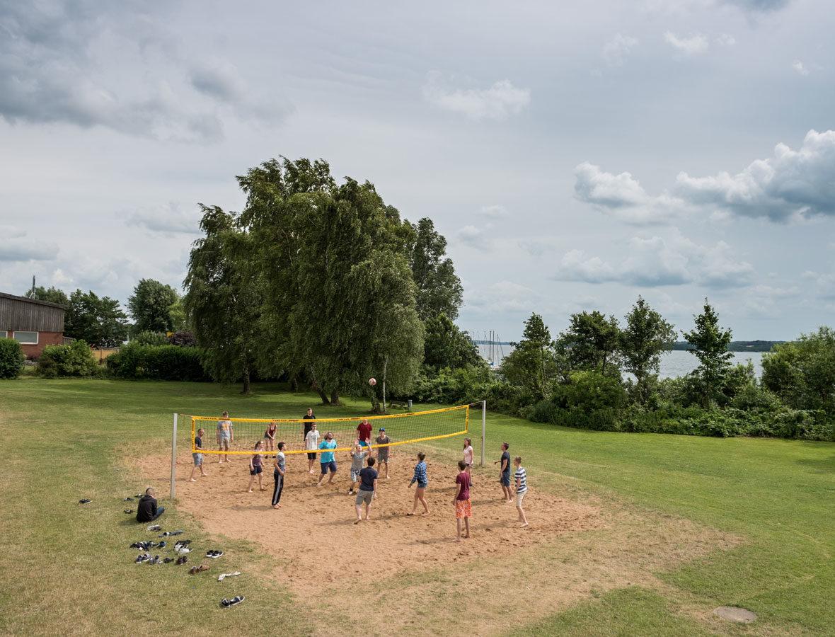 Foto: Mehrere Kinder spielen auf einem Beach-Volleyballplatz.