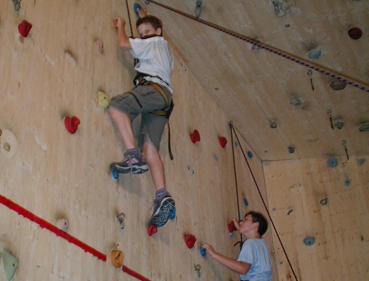 Foto: Ein Junge klettert in der Kletterhalle und ist mit einem Seil gesichert.