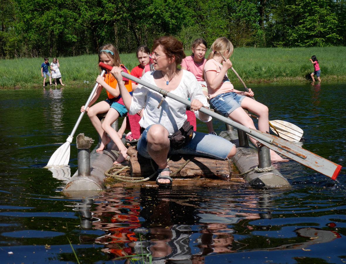 Foto: Eine Frau und mehrere Kinder sitzen auf einem Floß im Wasser, sie halten Paddel in der Hand.