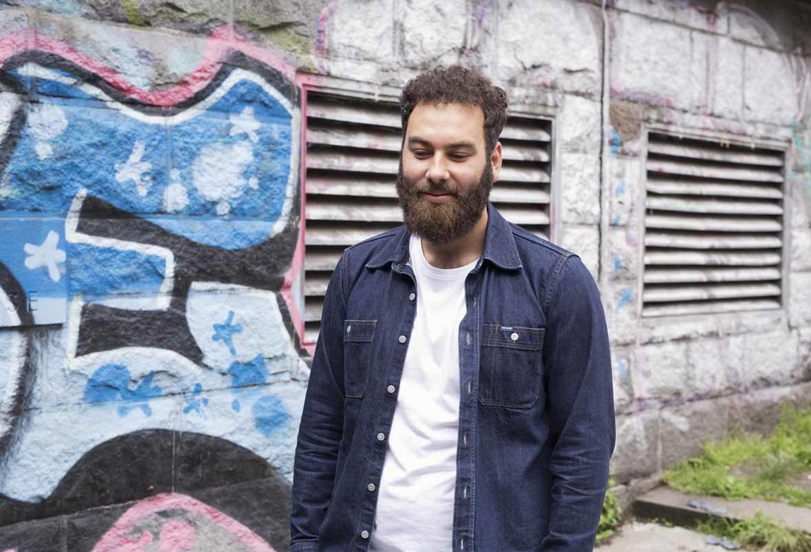 Mann mit Bart blickt nach unten und steht vor einer Graffiti-Wand