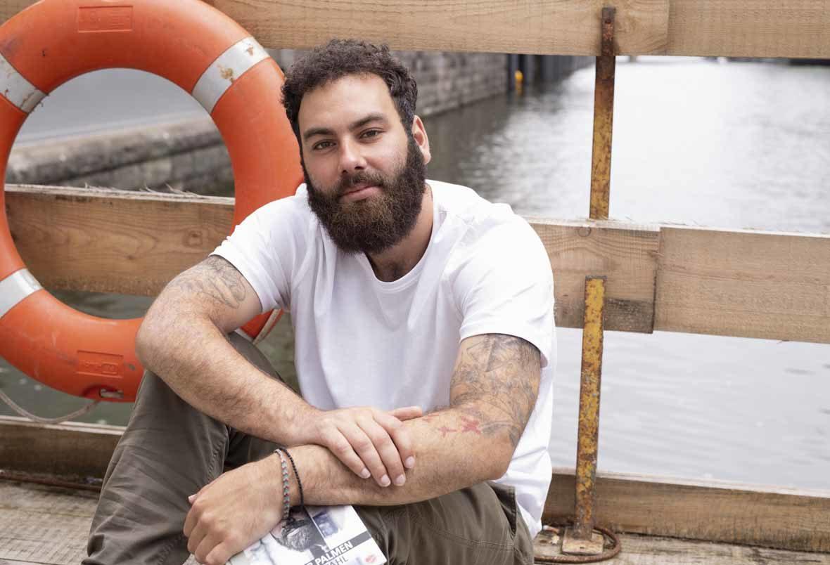 Foto: Mann mit Bart sitzt auf einer hölzernen Brücke, neben ihm ein Rettungsreifen