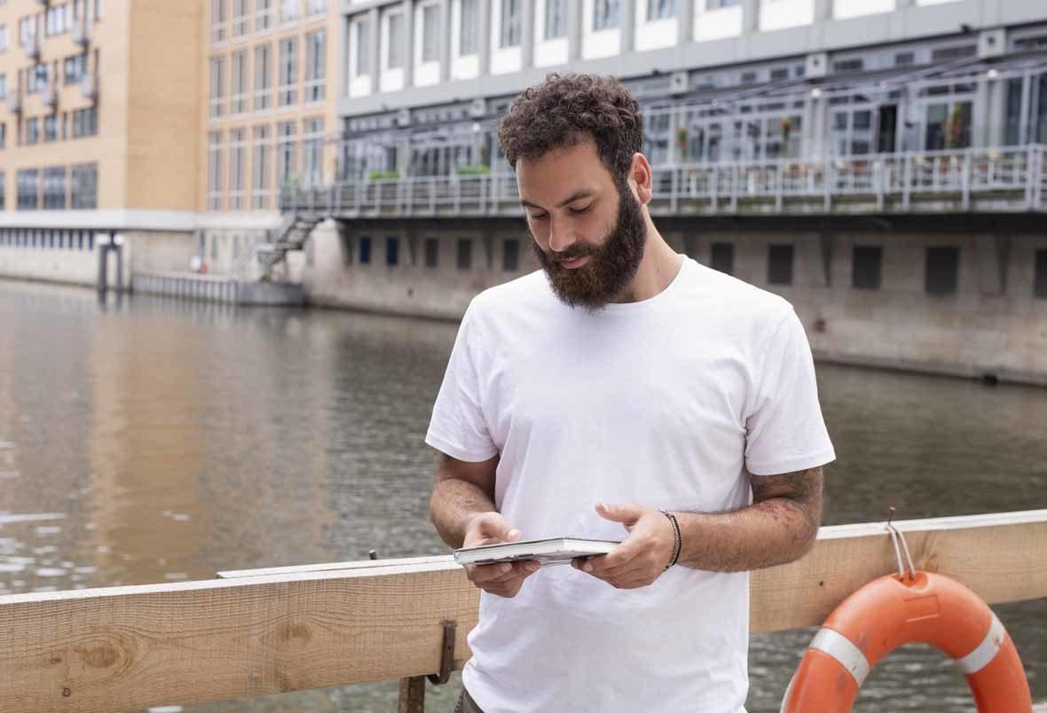 Foto: Mann mit Bart in T-Shirt hält ein geschlossenes Buch in der Hand und schaut darauf.