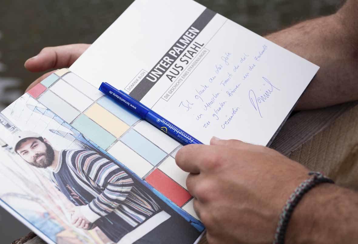 Foto: Ein geöffnetes Buch, in das etwas hineingeschrieben wurde.