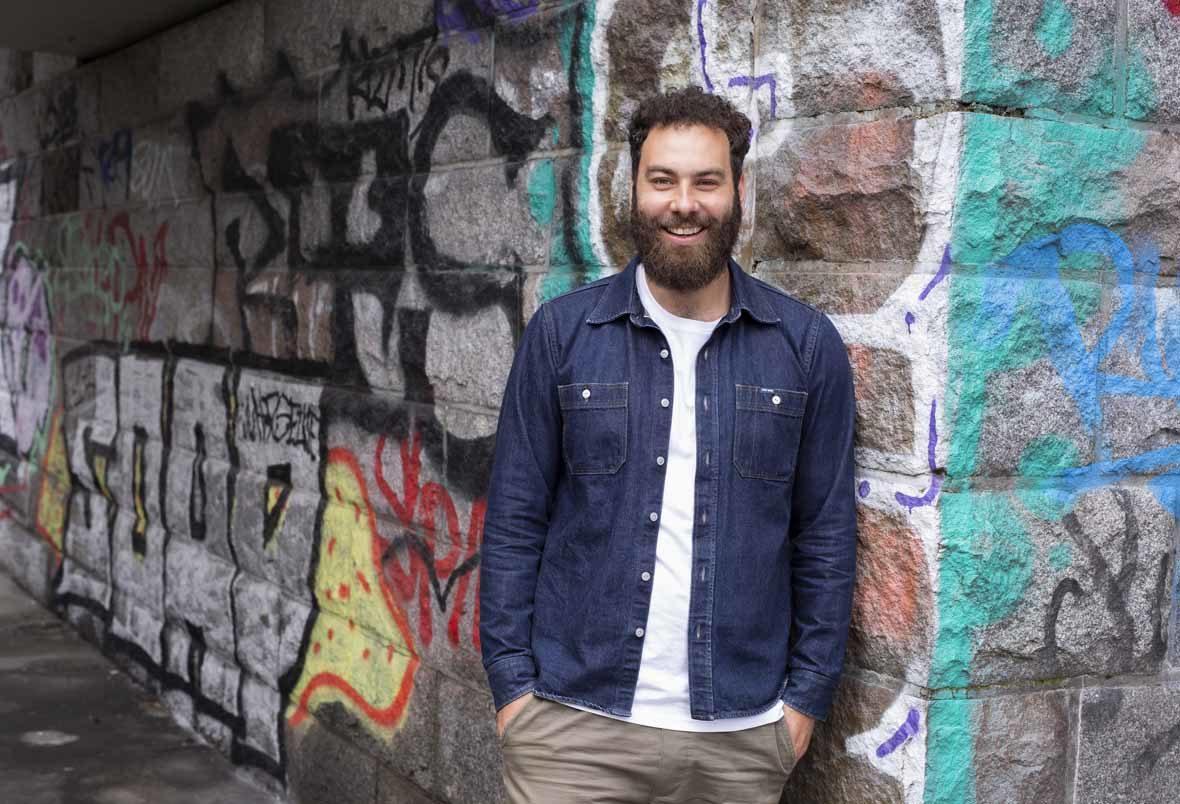 Foto: Mann mit Bart lehnt an einer Steinwand, auf der Graffitis sind