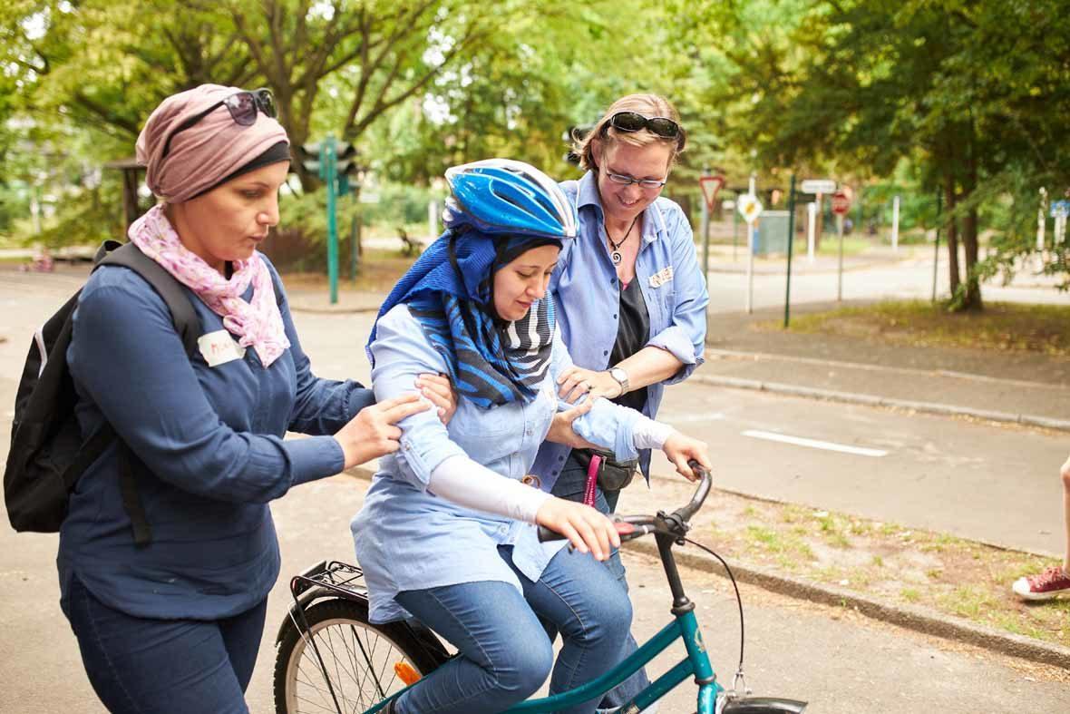 Zwei Frauen stützen eine dritte Frau, die auf einem Fahrrad sitzt