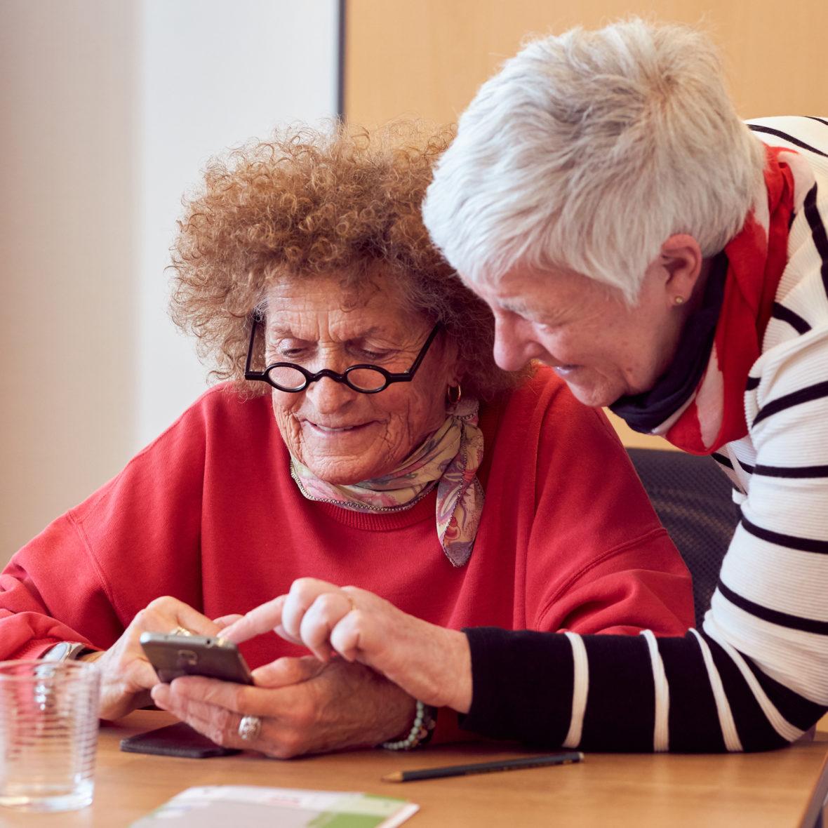 Zwei Seniorinnen schauen auf ein Smartphone.