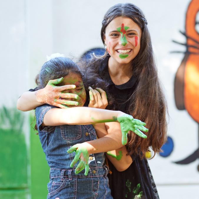 Zwei Mädchen malen mit Fingerfarbe und haben Spaß.