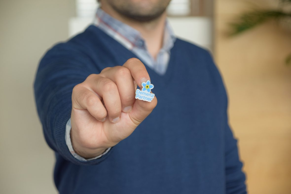 Mann hält Demenz Partner Button ins Bild
