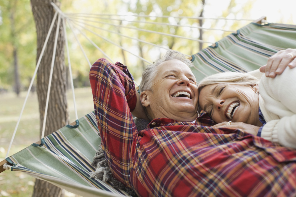 Happy Mature Couple Lying In Hammock At Park During Autumn