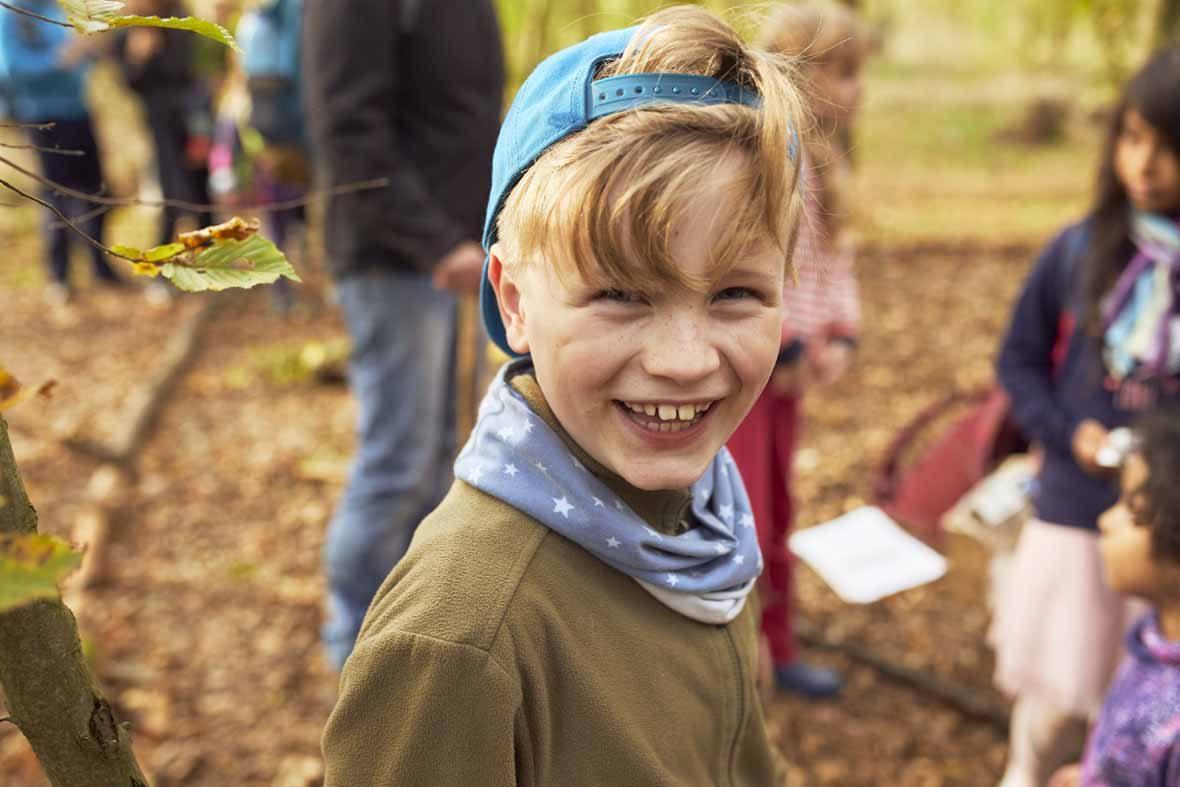 Ein Junge steht im Wald, schaut in die Kamera und lacht.