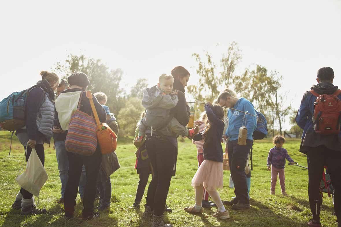 Foto: Eine Gruppe von Erwachsenen und Kindern mit Rucksäcken stehen auf einer Lichtung.