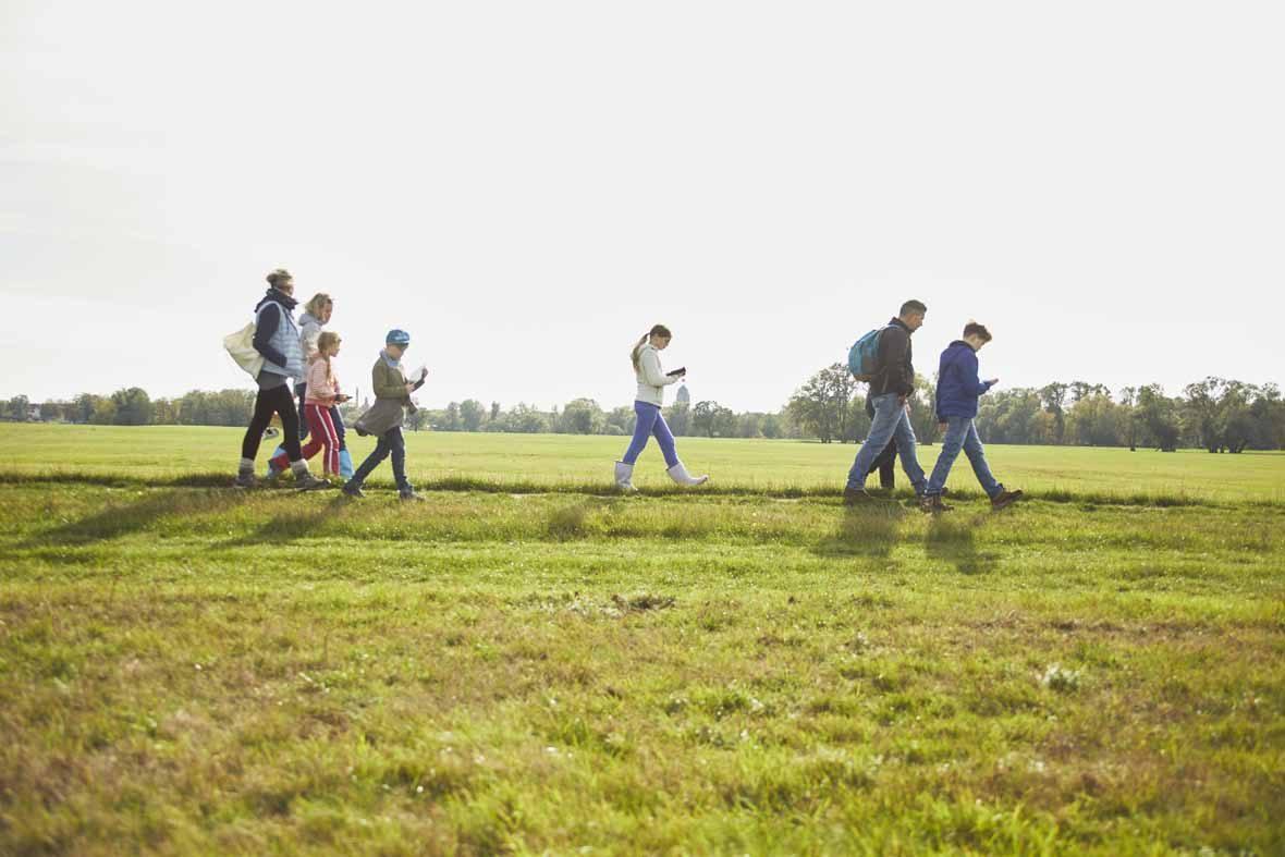 Foto: Eine Gruppe Erwachsene und Kinder gehen über eine Wiese.