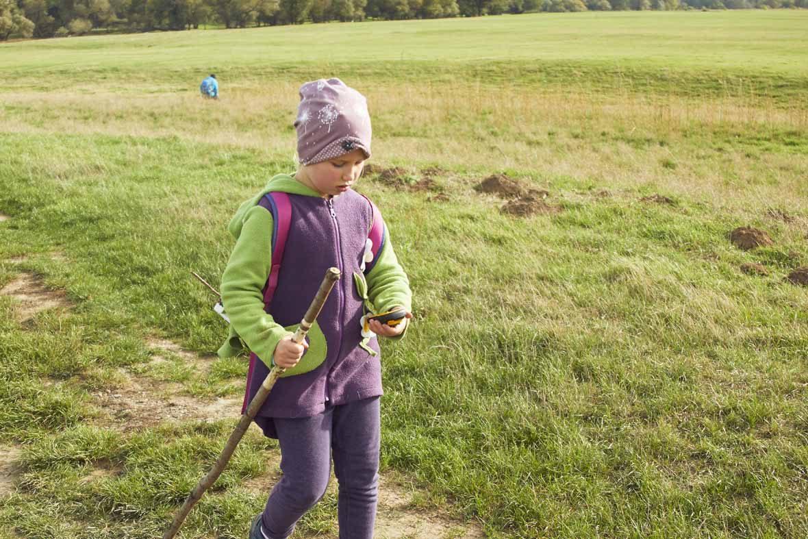 Foto: Ein Mädchen mit Wanderstock geht über eine Wiese und schaut auf einen GPS-Tracker in seiner Hand.