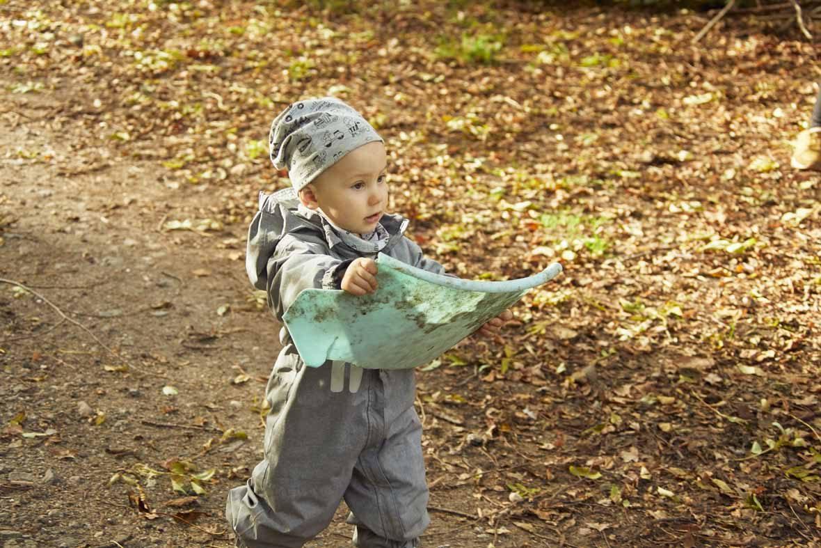 Foto: Ein Kleinkind läuft mit einer Karte in der Hand über einen Waldweg.