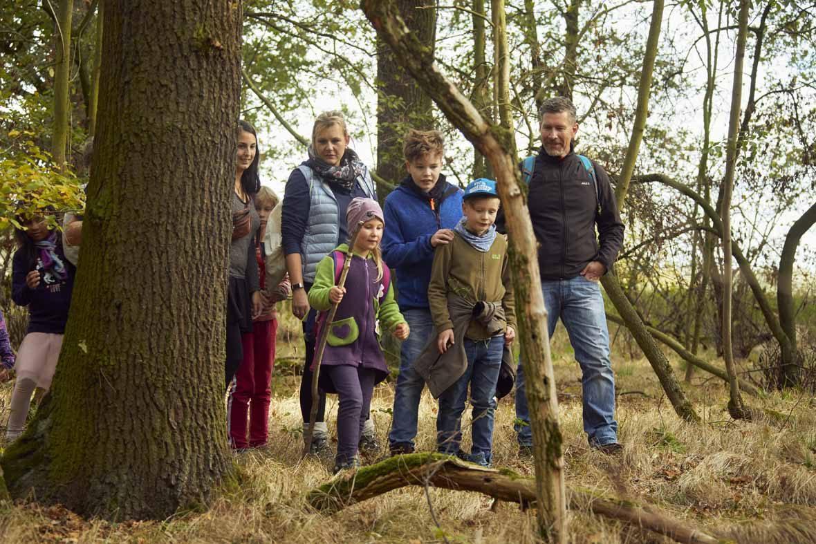 Foto: Eine Gruppe Erwachsene und Kinder laufen durch den Wald.