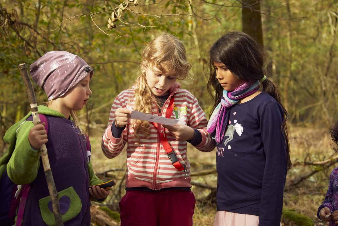 Foto: Drei Mädchen schauen auf einen Zettel, eines liest von diesem vor.