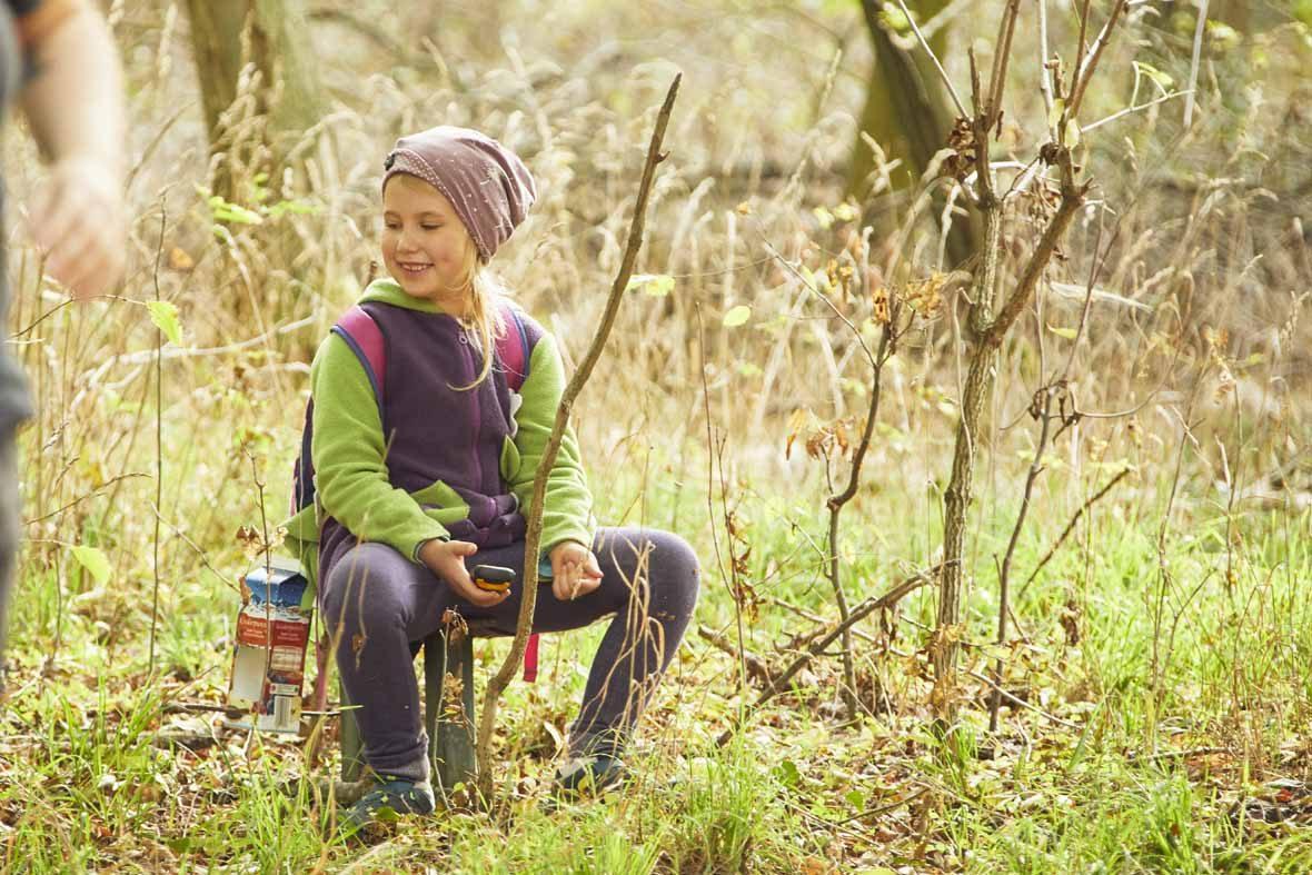 Foto: Ein Mädchen sitzt im Wald und lächelt.