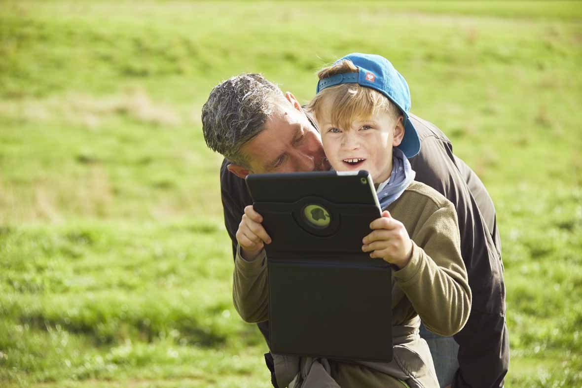 Foto: Ein Junge hält ein Tablet in der Hand, der Vater beugt sich zu ihm.