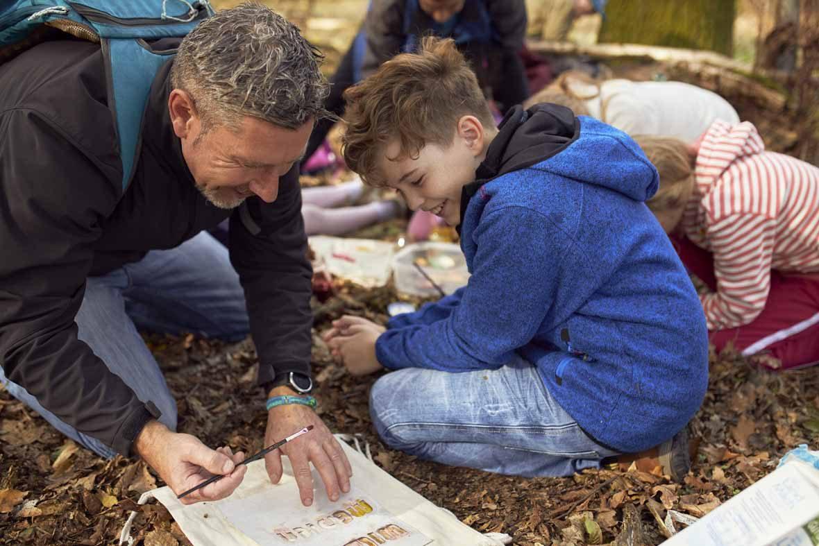 Foto: Ein Vater und sein Sohn bemalen einen Jutebeutel, der auf dem Waldboden liegt.