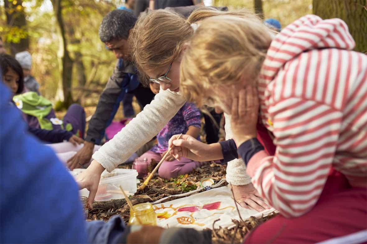 Foto: Auf dem Waldboden liegen Jutebeutel, die von Kindern bemalt werden.