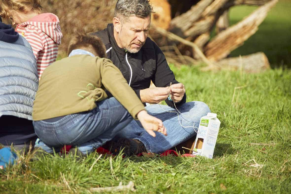Foto: Ein Mann sitzt auf einer Wiese und bastelt etwas aus einer alten Milchtüte.