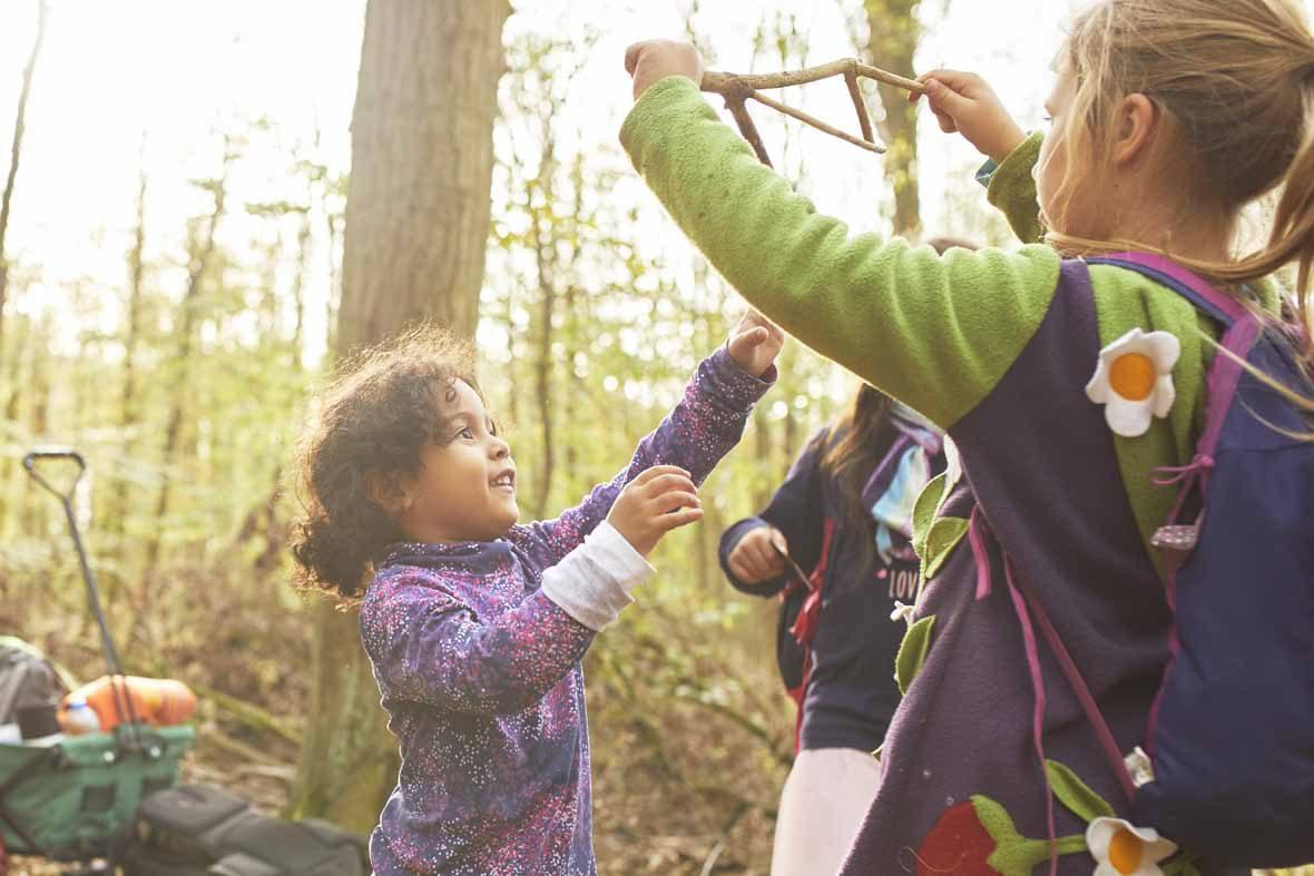 Foto: Drei Mädchen im Wald, eines hält einen Stock hoch, das andere greift danach.