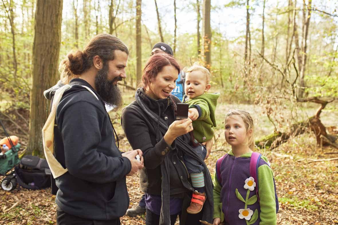 Foto: Eine Familie mit zwei Kindern schaut sich ein Polaroidfoto an.