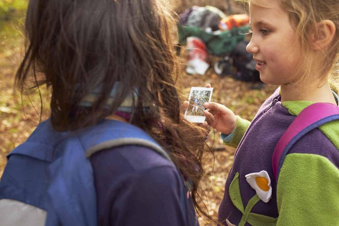 Foto: Zwei Mädchen schauen sich ein Polaroidfoto an.