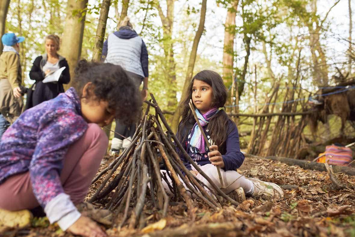 Foto: Zwei Mädchen bauen einen Holzstapel aus Stöcken.