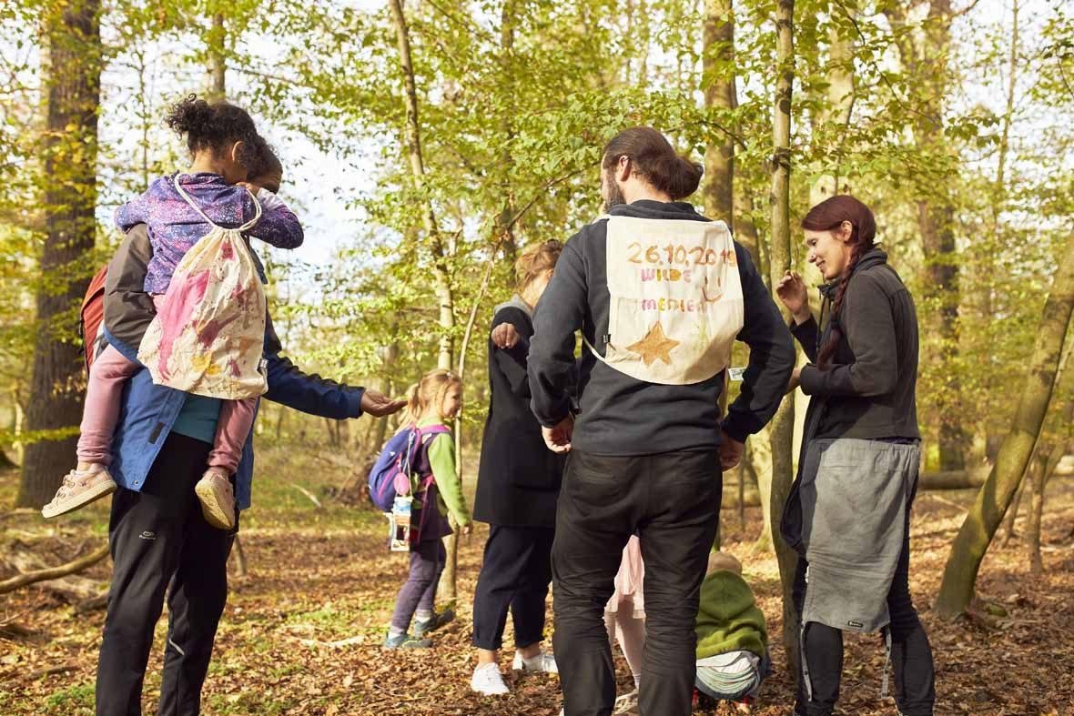 Foto: Eine Gruppe Menschen im Wald mit bemalten Jutebeuteln auf dem Rücken.