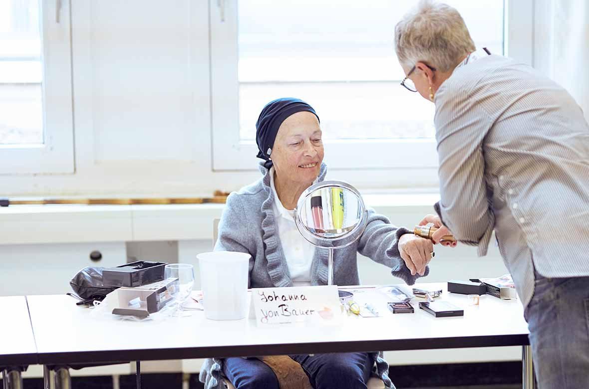 Foto: Eine alte Frau sitzt am Tisch vor einem Schminkspiegel, eine zweite Frau berät sie