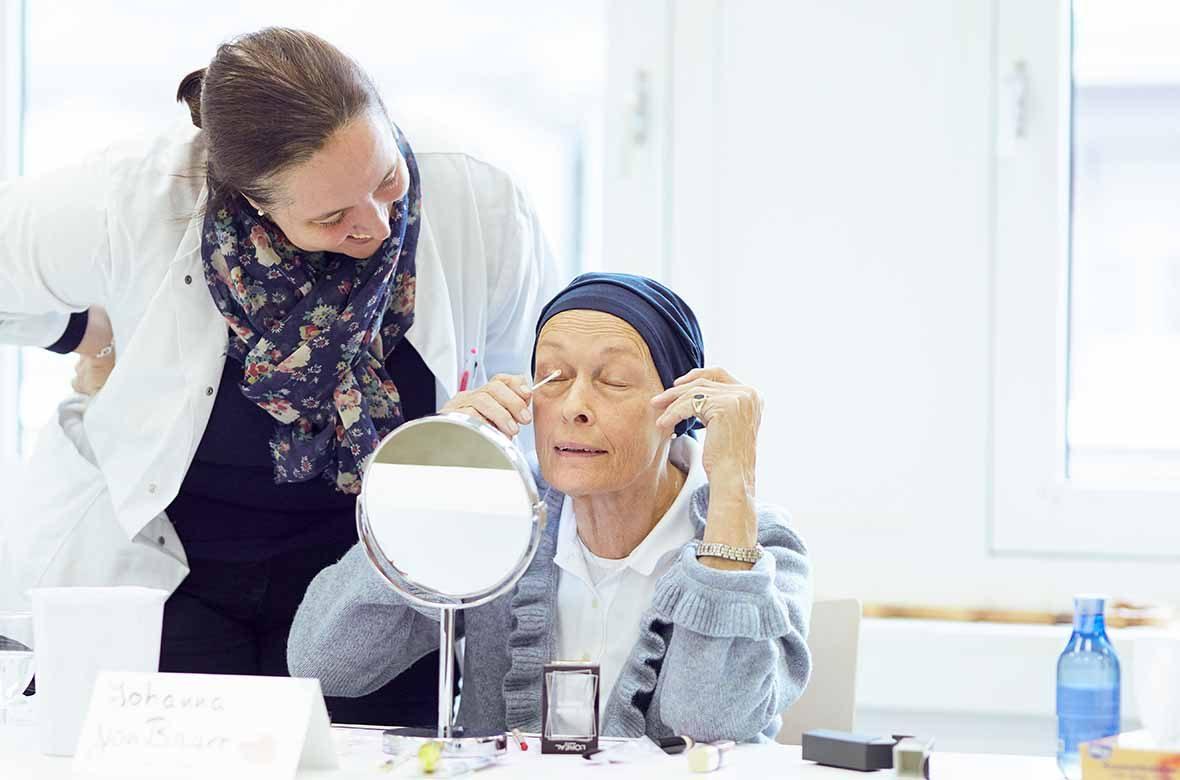 Eine Frau beugt sich zu einer zweiten Frau, die sich gerade schminkt