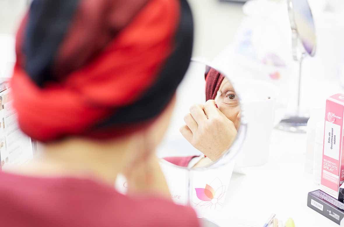 Foto: Eine Frau mit Turban schaut in einen Schminkspiegel.