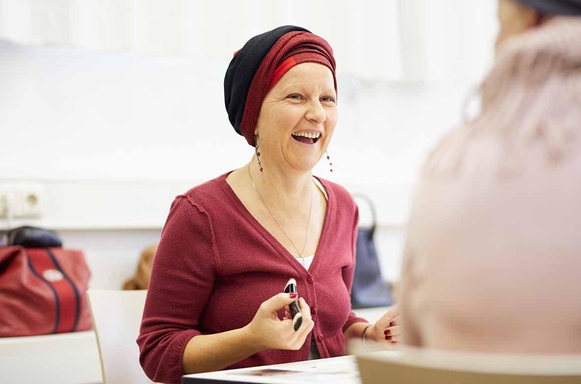 Eine Frau sitzt am Tisch, hält einen Pinsel in der Hand und lacht