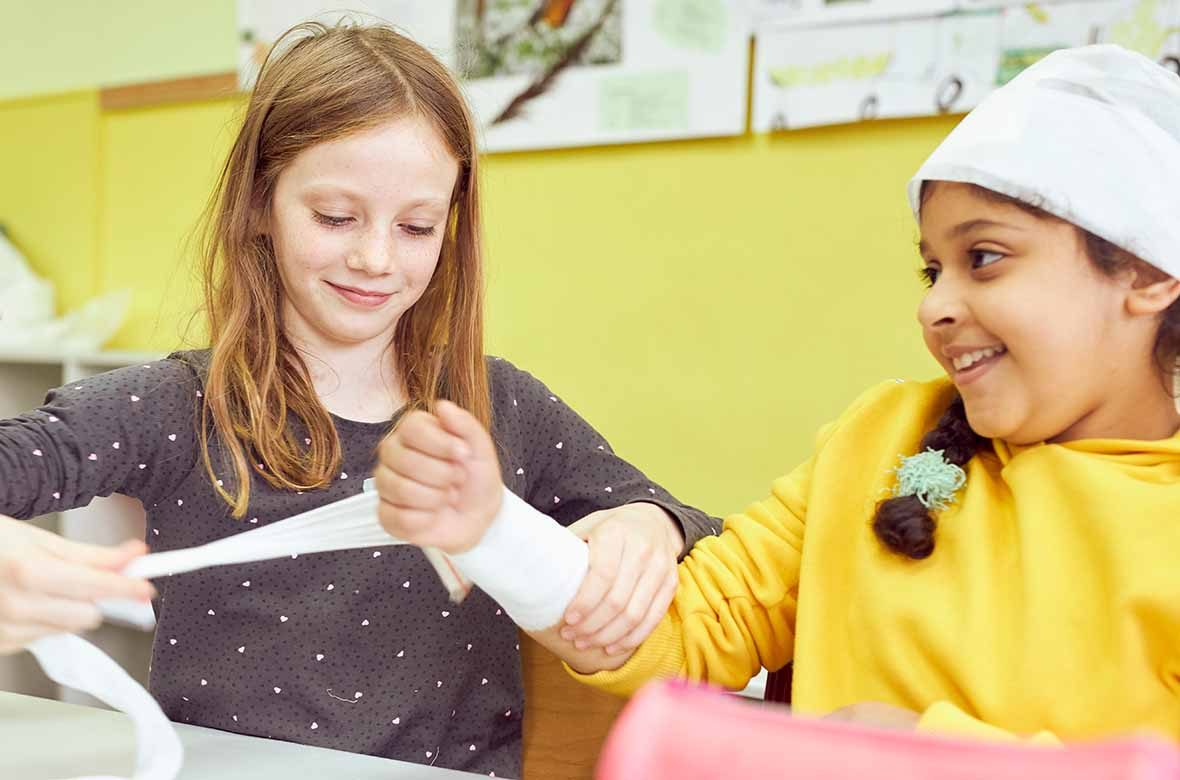 Ein Mädchen legt einen Druckverband am Arm eines anderen Mädchens an.