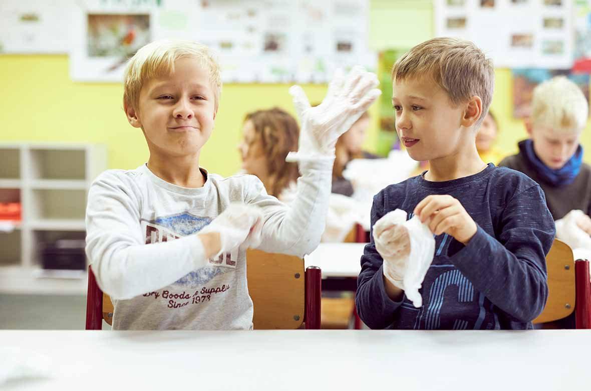 Zwei Jungen ziehen sich Einmalhandschuhe an.