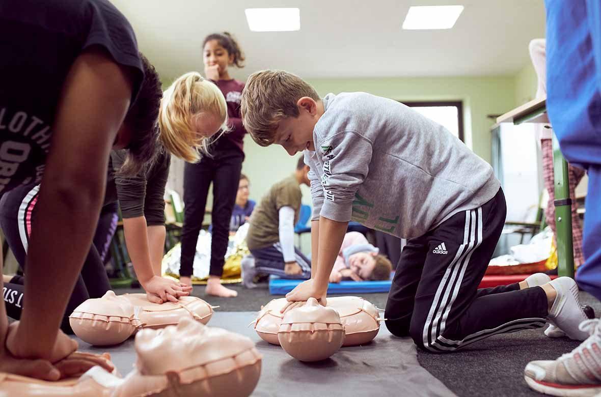 Schüler führen eine Herzdruckmassage an Puppen durch