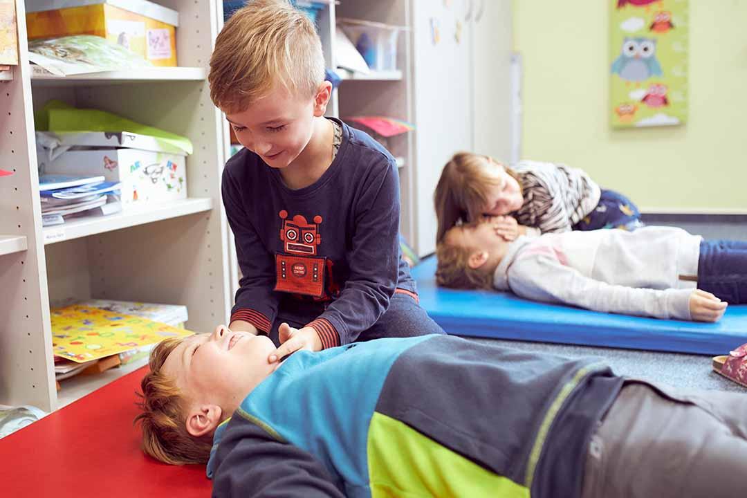 Ein Junge überprüft bei einem anderen Jungen die Atmung.