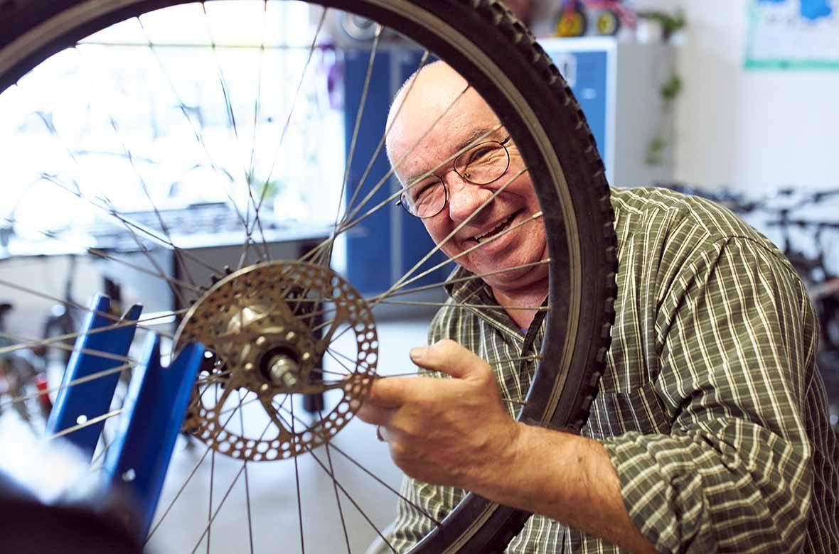 Ein Mann hält ein Fahrrad-Rad in der Hand und lacht