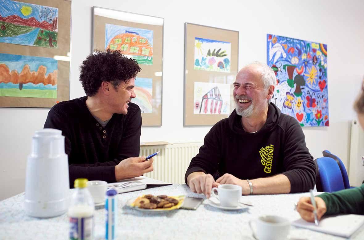 Zwei Männer sitzen am Tisch und lachen sich an.