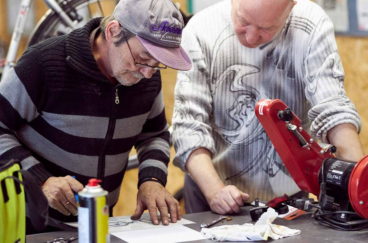 Zwei Männer schauen auf ein Blatt papier auf einem TIsch.